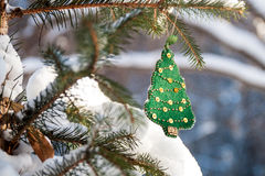 Christmas tree branch in the forest with green handmade decoration. Sunny winter day Stock Photos