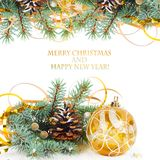 Christmas tree branch with gold serpentine and yellow sphere Stock Photos