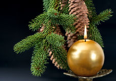 Christmas tree branch with golden burning candle Royalty Free Stock Image