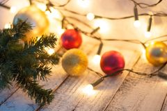 Christmas tree branch, lights and baubles on white wooden table with copy space. stock photography