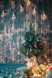 Christmas tree branch and lights on wooden background. View with copy space royalty free stock image