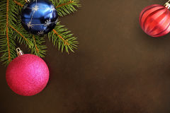 Christmas tree branch with pink, blue and red wavy ball on a dark background. Top view stock photo