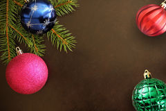 Christmas tree branch with pink, blue, red wavy and green ribbed ball on a dark background Royalty Free Stock Photography