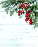 Christmas tree branch with red berries. Winter holidays decorati. Christmas tree branch with red berries on wooden background. Winter holidays decoration. Retro Stock Image