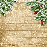 Christmas tree branch with snowfall on the wooden board Stock Image