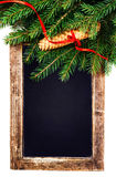 Christmas Tree Branch on  Vintage Blackboard isolated on white b Stock Photography