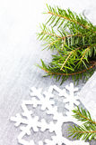 Christmas tree branch and White Christmas ornaments on soft grey Royalty Free Stock Images