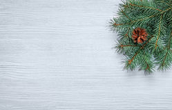 Christmas tree branch on a wooden background. Top view Royalty Free Stock Images