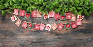 Christmas tree branches Advent calendar wooden background. Christmas tree branches and Advent calendar on dark wooden background royalty free stock image