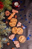 Christmas tree branches, biscuits stars blue cinnamon sticks on a black leather background with a place for the text royalty free stock images