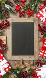Christmas tree branches blackboard gifts red decoration. Christmas tree branches, blackboard, gifts and red decoration royalty free stock photography
