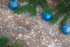 Christmas tree branches, blue balls on snowbound winter wooden b Stock Image