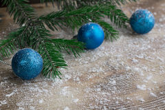 Christmas tree branches, blue balls on winter snowbound wooden b Stock Photography