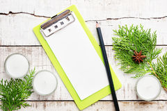 Christmas tree branches, candles and green clip board on white w Stock Photos