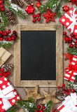 Christmas tree branches chalkboard gifts red decoration. Christmas tree branches, chalkboard, gifts and red decoration royalty free stock photography