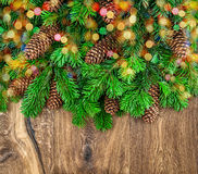 Christmas tree branches with cones and colorful lights Royalty Free Stock Photography