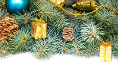 Christmas tree branches with cones, gifts and toys on a white ba Royalty Free Stock Photo