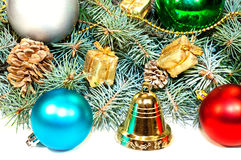 Christmas tree branches with cones, gifts and toys on a white ba Stock Image