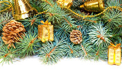 Christmas tree branches with cones, gifts and toys on a white ba Stock Photo