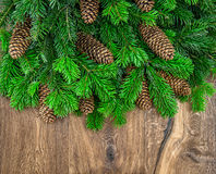 Christmas tree branches with cones over wooden background Royalty Free Stock Image