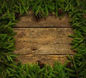 Christmas tree branches with cones on wooden texture ready for y Royalty Free Stock Photo