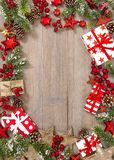Christmas tree branches gifts red decoration wooden background. Christmas tree branches, gifts and red decoration on wooden background stock images