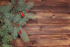 Christmas tree branches green with red berries on a wooden background boards. Christmas winter green tree branches with red fresh winter berries on wooden planks stock photos