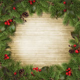 Christmas tree branches and holly on wooden board Royalty Free Stock Photography