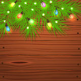 Christmas tree branches and light bulb on wooden. Stock Photo