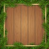 Pine tree branches square frame on wooden background. Christmas tree branches like square frame on wooden planks background. Template for Christmas greeting card Royalty Free Stock Photos