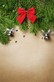 Christmas tree branches. With new year toys and silver bells on brown paper background Stock Images