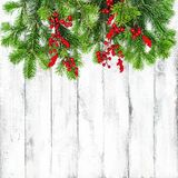 Christmas tree branches red berries decoration. Christmas tree branches with red berries decoration on wooden background Stock Photo