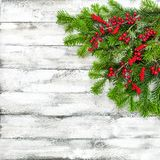 Christmas tree branches red berries decoration white wooden text. Christmas tree branches with red berries decoration on white wooden texture. Winter holidays Stock Photography