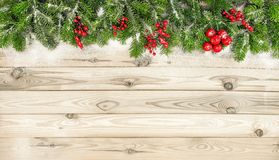 Christmas tree branches red berries decoration wooden background. Christmas tree branches and red berries decoration on wooden background royalty free stock image