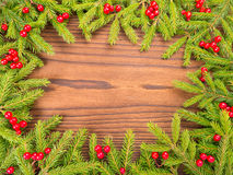 Christmas tree branches and red berries frame on the dark backgr Royalty Free Stock Photography
