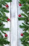 Vertical borders of Christmas red ornaments hanging in evergreen. Christmas tree branches and red ornaments forming vertical borders on rustic white wood royalty free stock photos