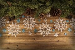 Christmas tree branches and snowflakes ornament on natural wooden table in background. stock photos