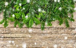 Christmas tree branches with snowflakes wooden background stock photography