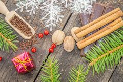 Christmas tree branches with spices. Chocolate and red decorations on a rustic wooden surface Stock Photography