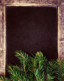 Christmas tree branches on Vintage Christmas Blackboard frame. R Royalty Free Stock Photos