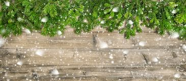 Christmas tree branches wooden background copy space falling sno. Christmas tree branches on wooden background. Winter header with copy space falling snow effect royalty free stock photo