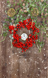 Christmas tree branches and wreath from red berrie. Green christmas tree branches and wreath from red berries over rustic wooden background. festive decoration royalty free stock image