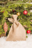 Christmas tree and burlap sack filled with gifts Royalty Free Stock Photography