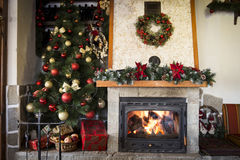 Christmas tree and burning fireplace at home Royalty Free Stock Images