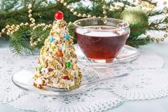 Christmas tree cake in festive decoration.  Cupcake in form of Christmas tree with cup of tea stock image
