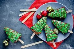 Christmas tree cakes. Festive pie pieces decorated with green frosting and sprinkles, Christmas holiday winter treats for kids stock image