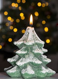 Christmas tree candle. Christmas candle in front of a blurred christmas tree Stock Photo