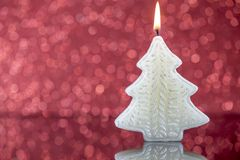 Christmas tree candle light with reflection on red blurred bokeh Royalty Free Stock Image