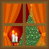 Christmas tree and candles at home. View indoor at home through the window and curtains Royalty Free Stock Images