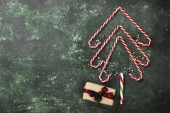 Christmas tree from candy canes and box with gift on a green bac. Kground. Top view, copy space Stock Photography